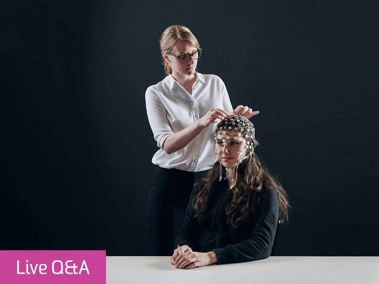 Psychologist attaching sensors to a patient's head