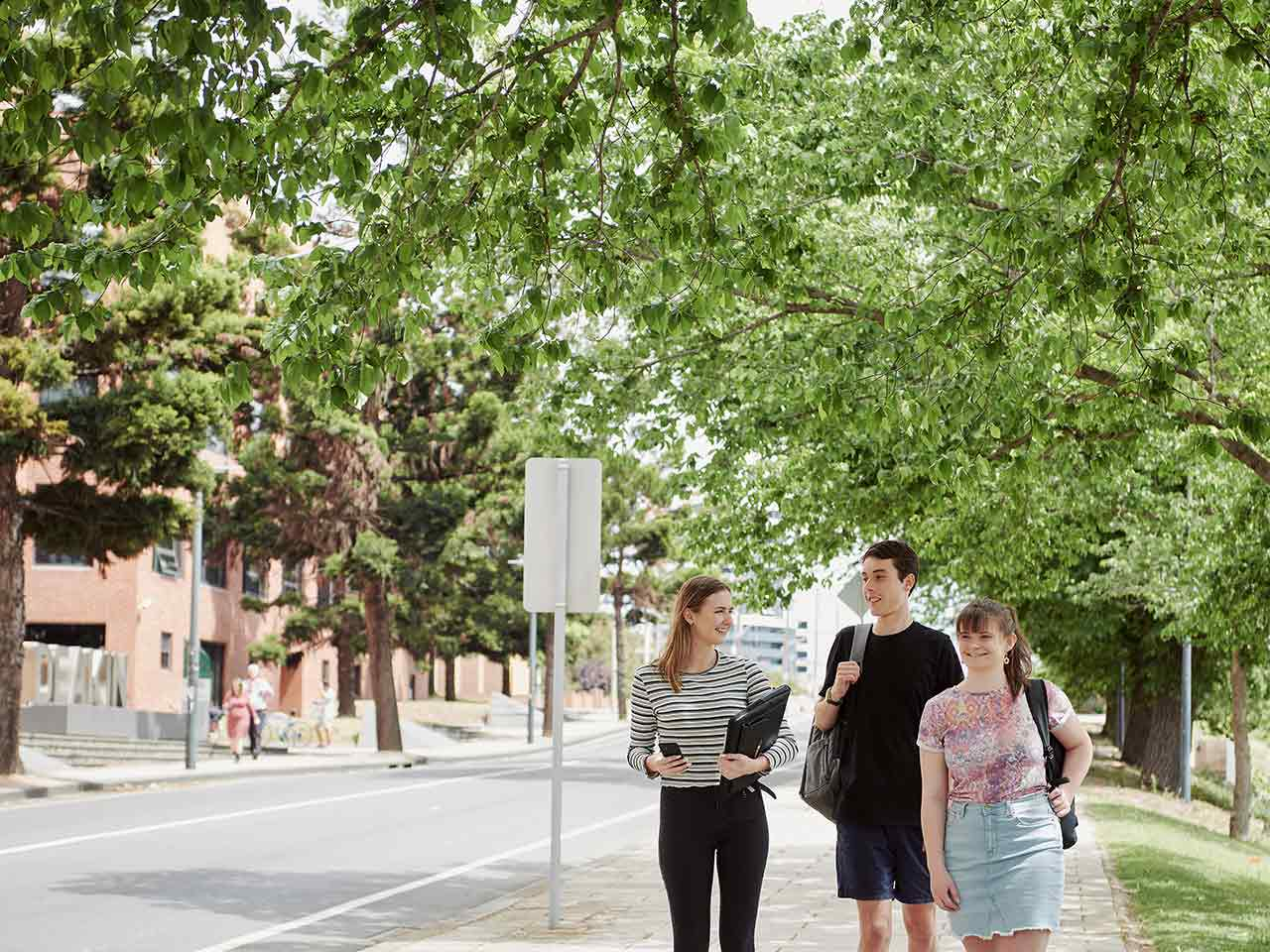 Three students walking outside of Geelong Waterfront Campus