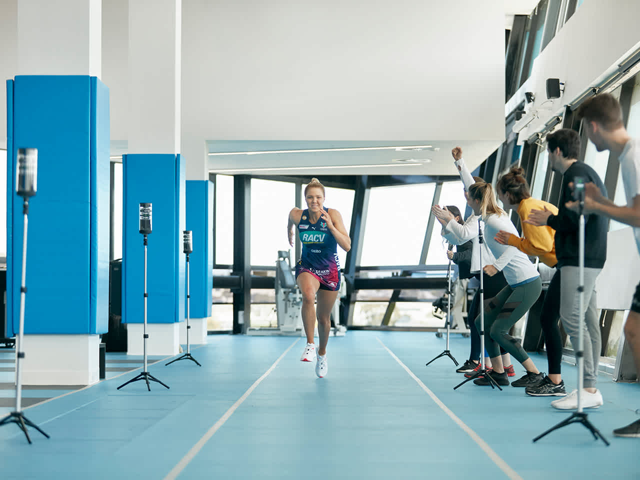 Students analysing athlete running down indoor track