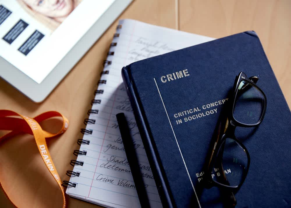 Crime textbook with notepad and glasses