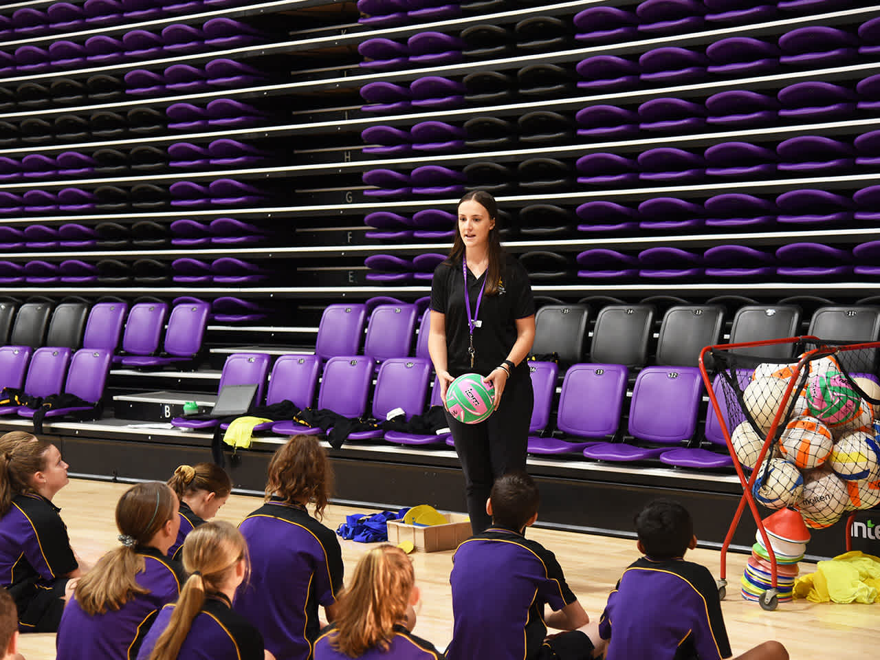 Teacher demonstrating netball drill to students on court
