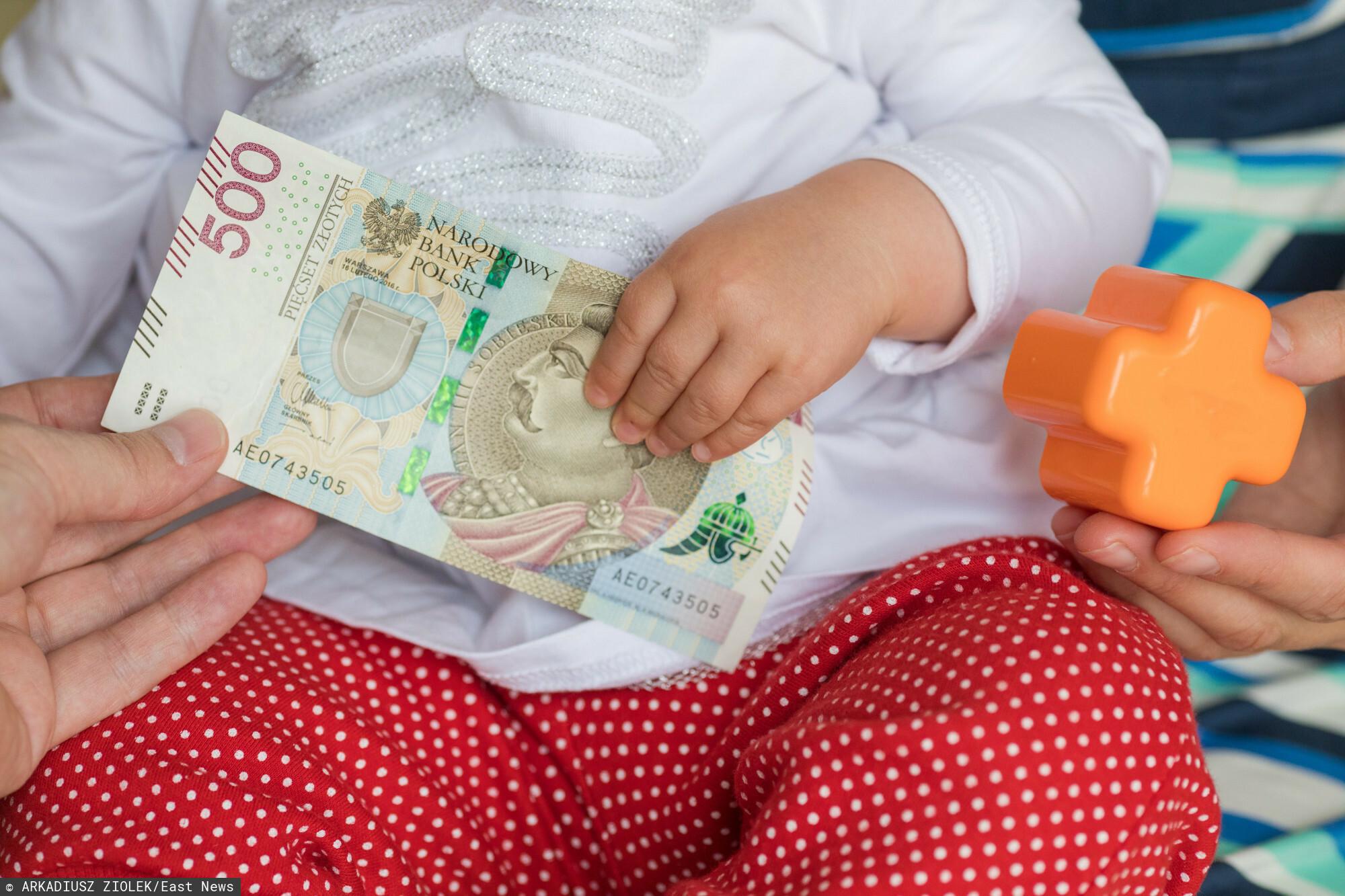 fot: Arkadiusz Ziolek/ East News. 16.07.2019. n/z Dlon dziecka i matki na tle zabawek i banknotu 500 zl.