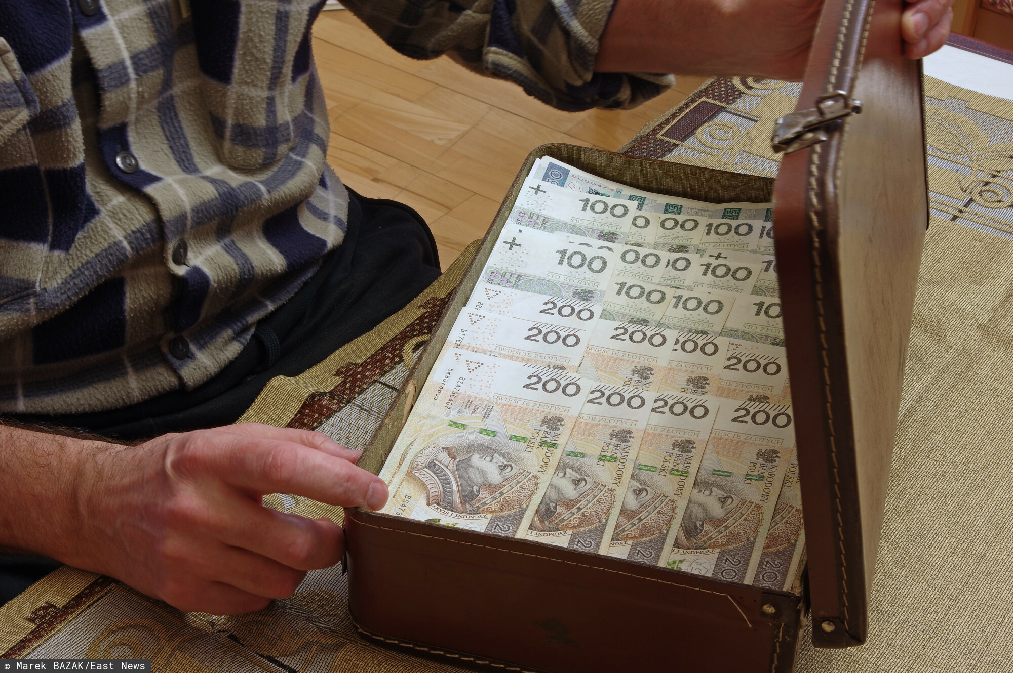 """Fot. Zofia i Marek Bazak/East News Bank w domu, walizka pelna pieniedzy, wielu seniorow trzyma swoje oszczednosci w domu, nie posiadajac kont bankowych padaja ofiara przestepcow wyludzajacych oszczednoscu calego zycia metodami """"na wnuczka"""" lub """"na policjanta""""."""