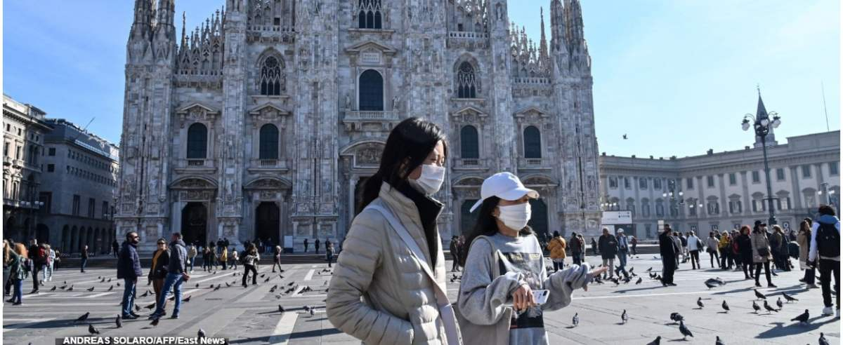 TOPSHOT - Two women wearing a protective facemask walk across the Piazza del Duomo, in front of the Duomo, in central Milan, on February 24, 2020 closed following security measures taken in northern Italy against the COVID-19 the novel coronavirus. - Italy reported on February 24, 2020 its fourth death from the new coronavirus, an 84-year old man in the northern Lombardy region, as the number of people contracting the virus continued to mount. (Photo by ANDREAS SOLARO / AFP)