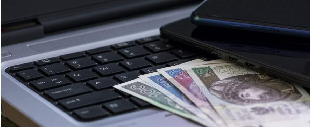 fot: Arkadiusz Ziolek/ East News. n/z Laptop, pieniadze, smartfon leza tablet na stole.