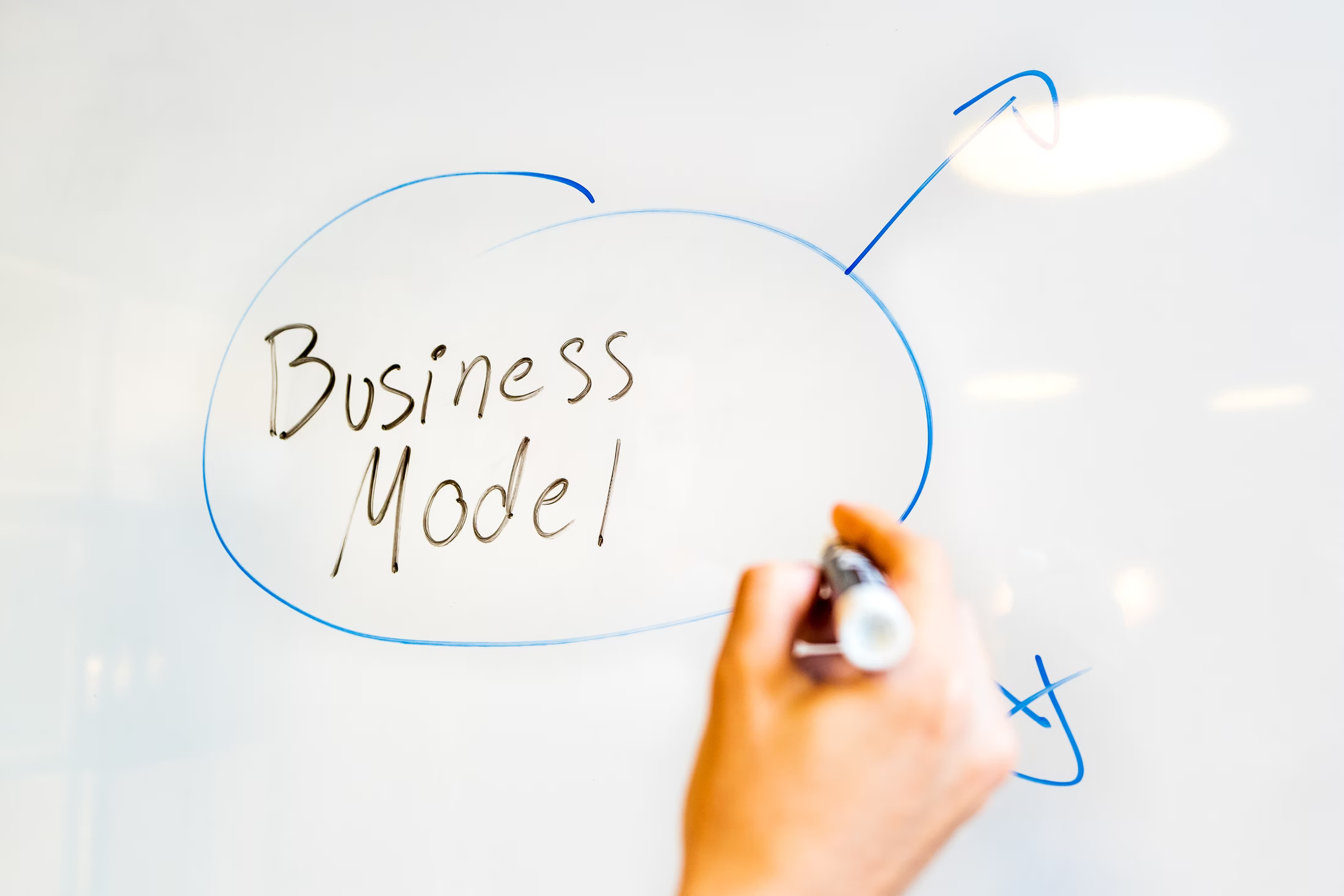 """person writing on white paper """"business model"""""""