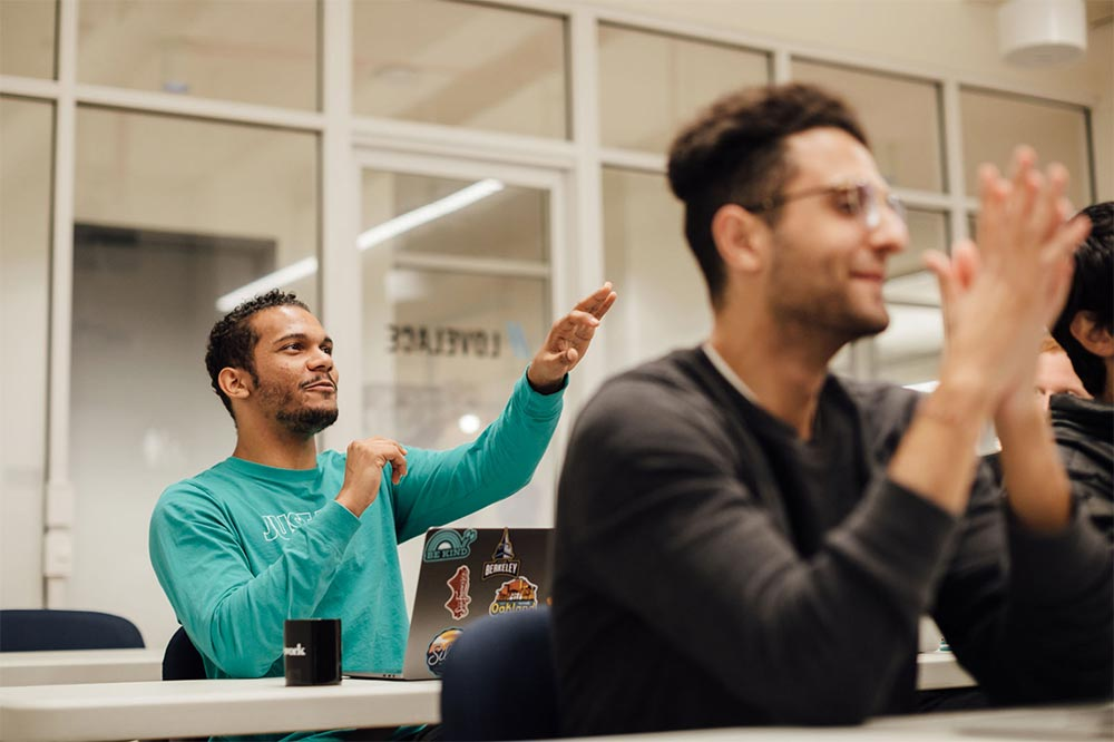 A student in a Flatiron School coding classroom raises his hand to ask a question.