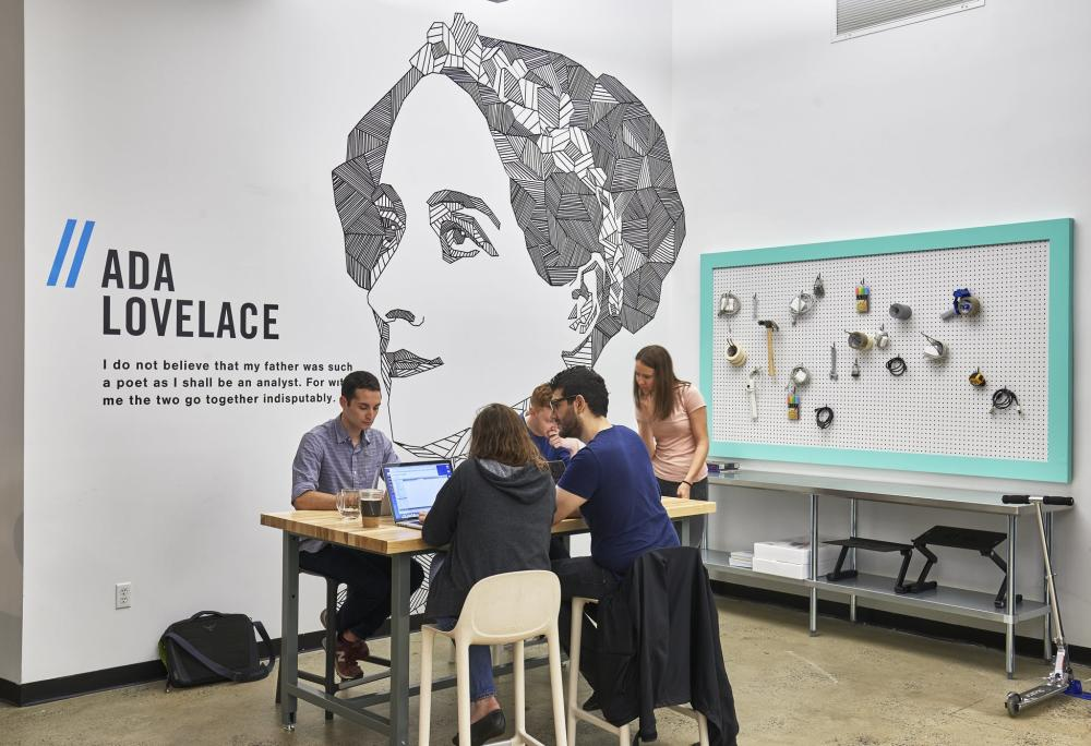 Wall with Ada Lovelace's portrait and students working in front of it