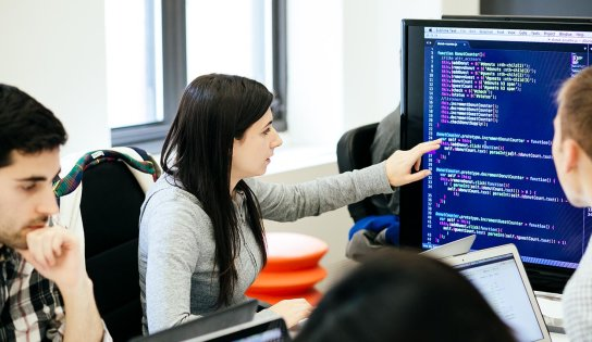 student points at code on a screen