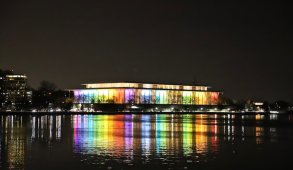 Glass building lit up with rainbow lights at night