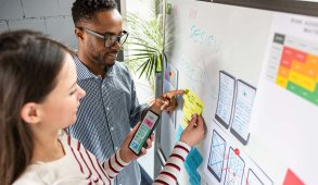 male and female UX/UI design team work on wireframe story boards over a whiteboard