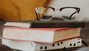 Books with a pair of glasses on top