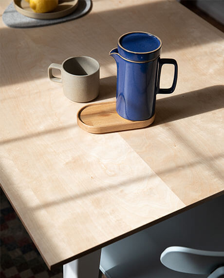 A pitcher and a cup on the Birch Floyd Rectangular Table.