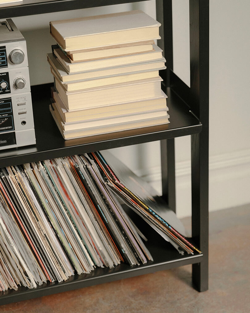 Each powder-coated steel shelf can safely hold 65 lbs. We recommend keeping heavier items (such as records!) on the lower shelves.