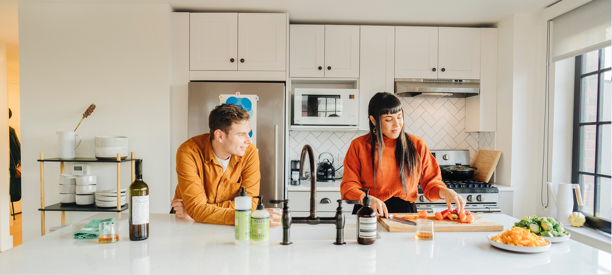 A photo of Brooklyn based couple Liron and Gal in their clean, well finished kitchen. Read more about them on the Floyd Blog, LivedIn.