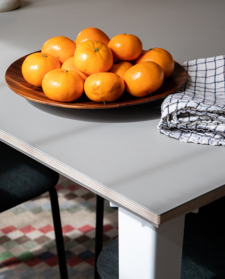 Corner shot of a small plate of oranges on a fog table.