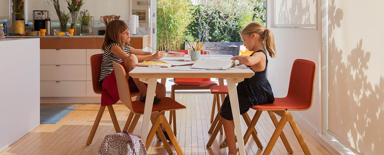 Two girls doing homework at the table.