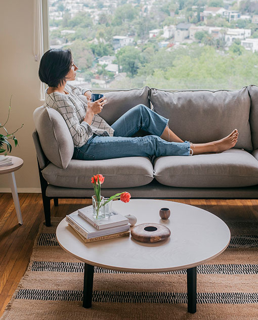 Lady sitting lengthwise on the Floyd Sofa while holding a cup of coffee