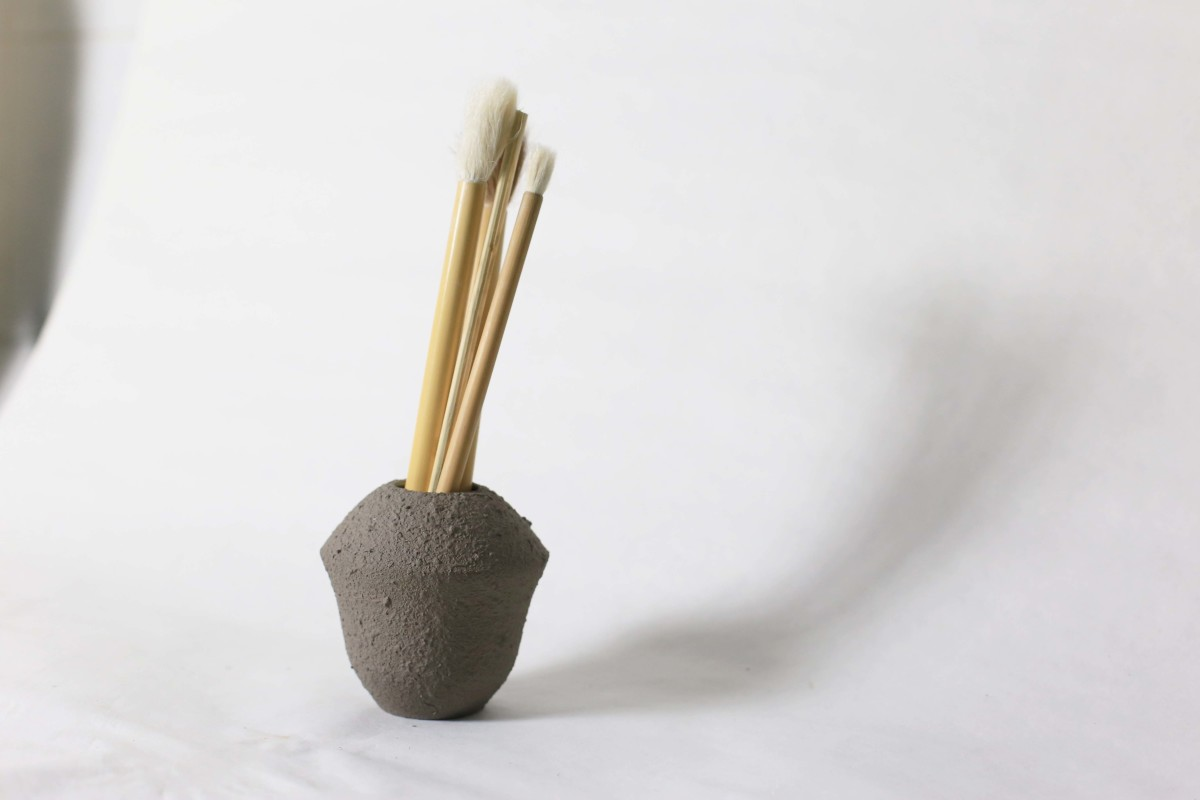 Small grey ceramic vase with brushes in it on a white background 2