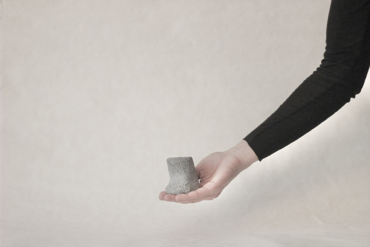a hand holds terrazzo blue clay candle holder on a gray background