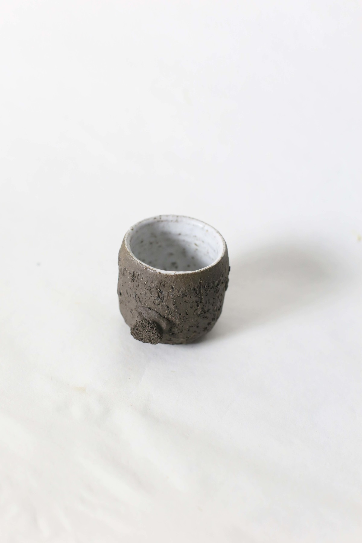 small brown ceramic cup with a bulge below on a white background over view