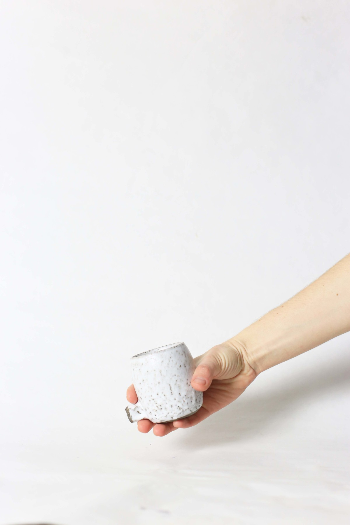 A hand holds white ceramic cup with knot below on a white background