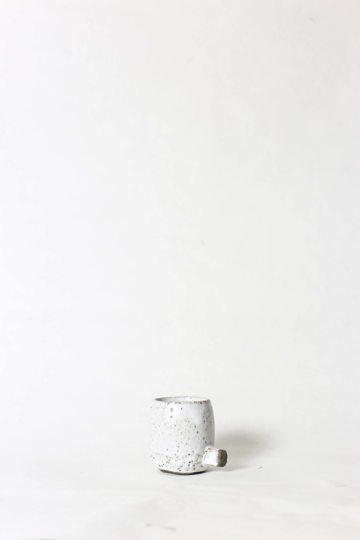 White ceramic cup with knot below on a white background