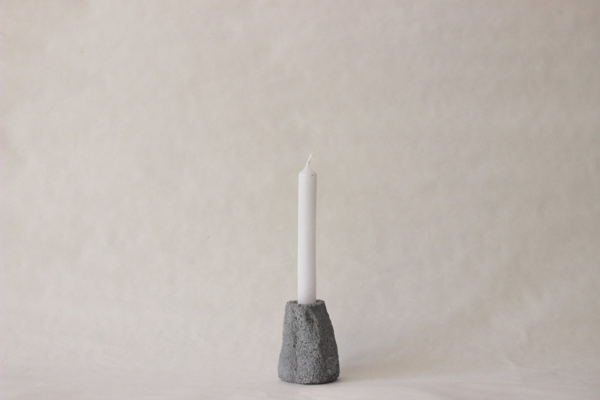 gray ceramic candle holder with candle on gray background 1