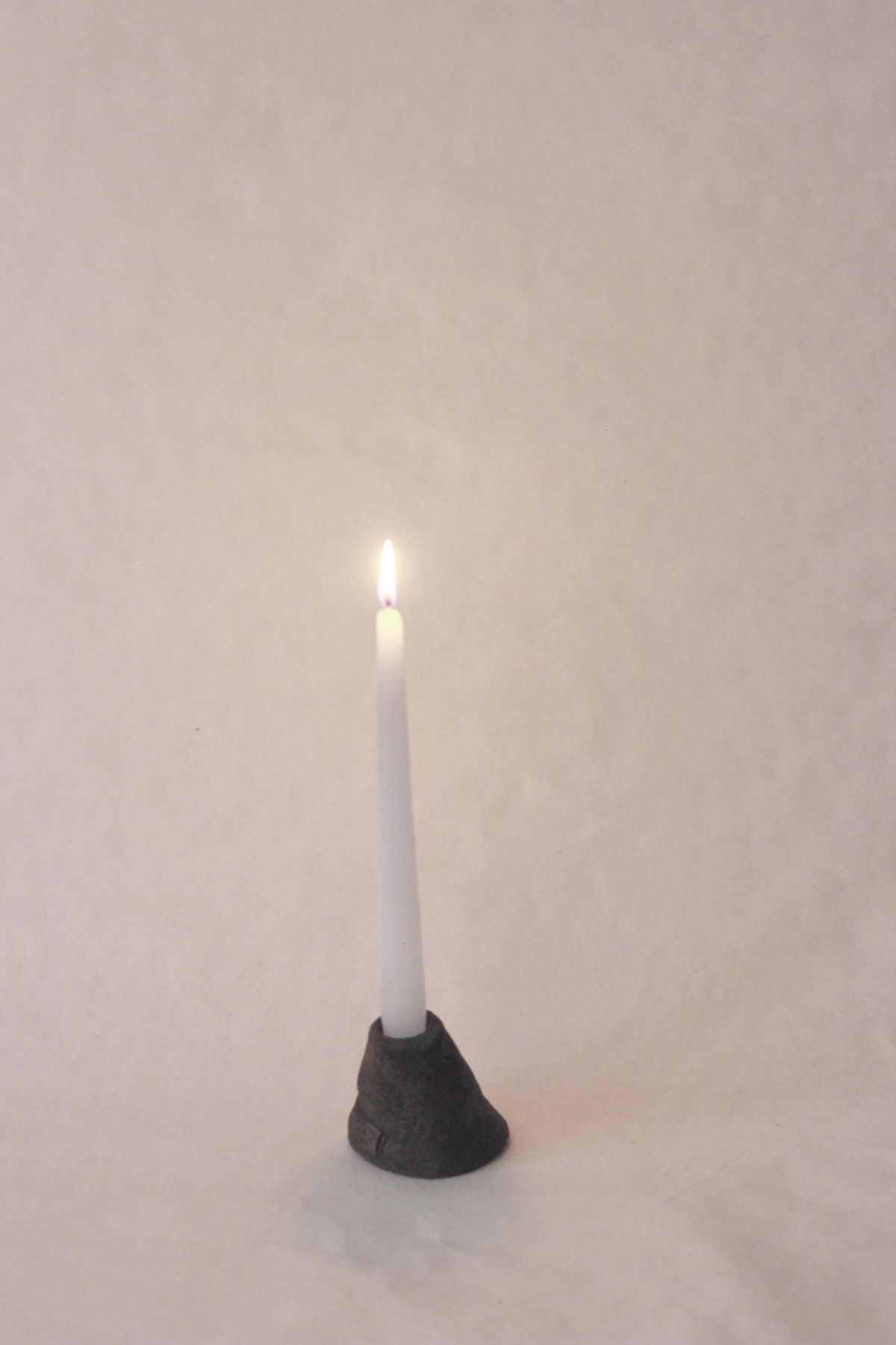 brown ceramic candle holder with lighted candle on a gray background 1