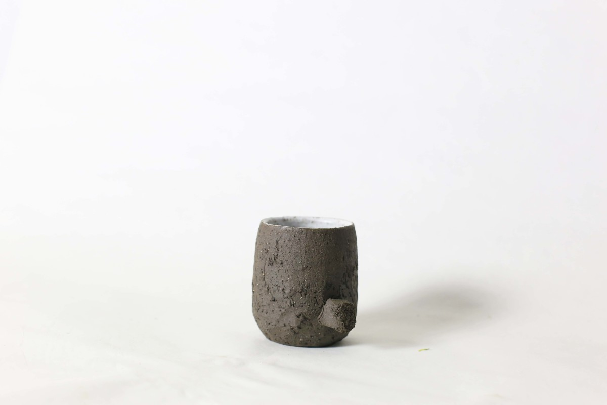 Terra nigra clay cup with a knot below on a white background close shot