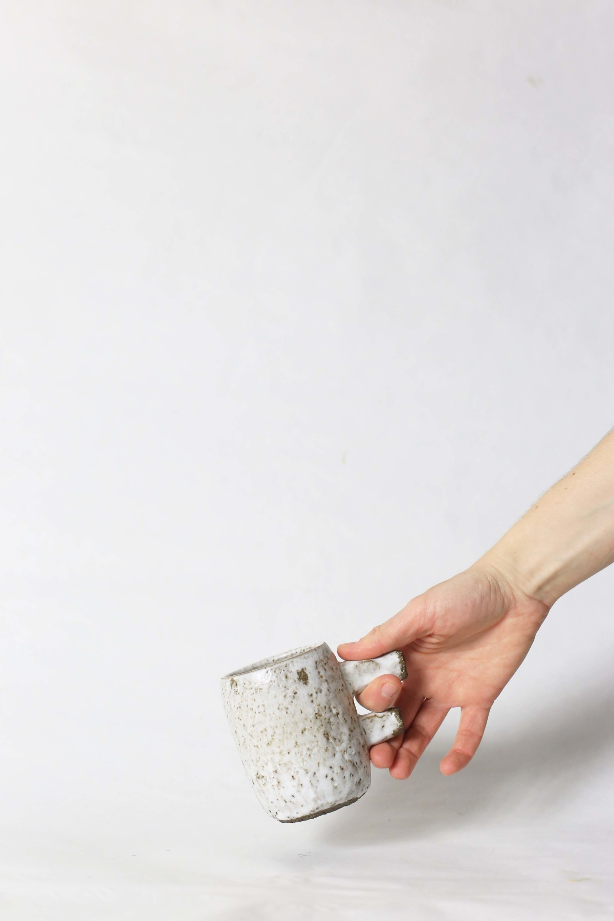a hand holds spotty white ceramic cup with two stick handle on a white background