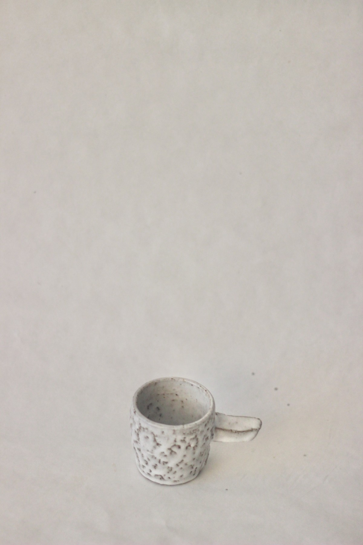 gray spotty ceramic coffee cup on a gray background over view 1