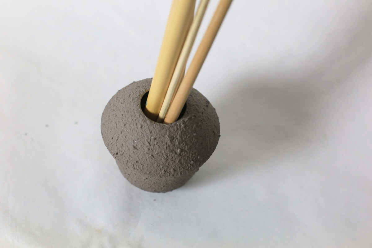 Small grey ceramic vase with brushes in it on a white background over view 1