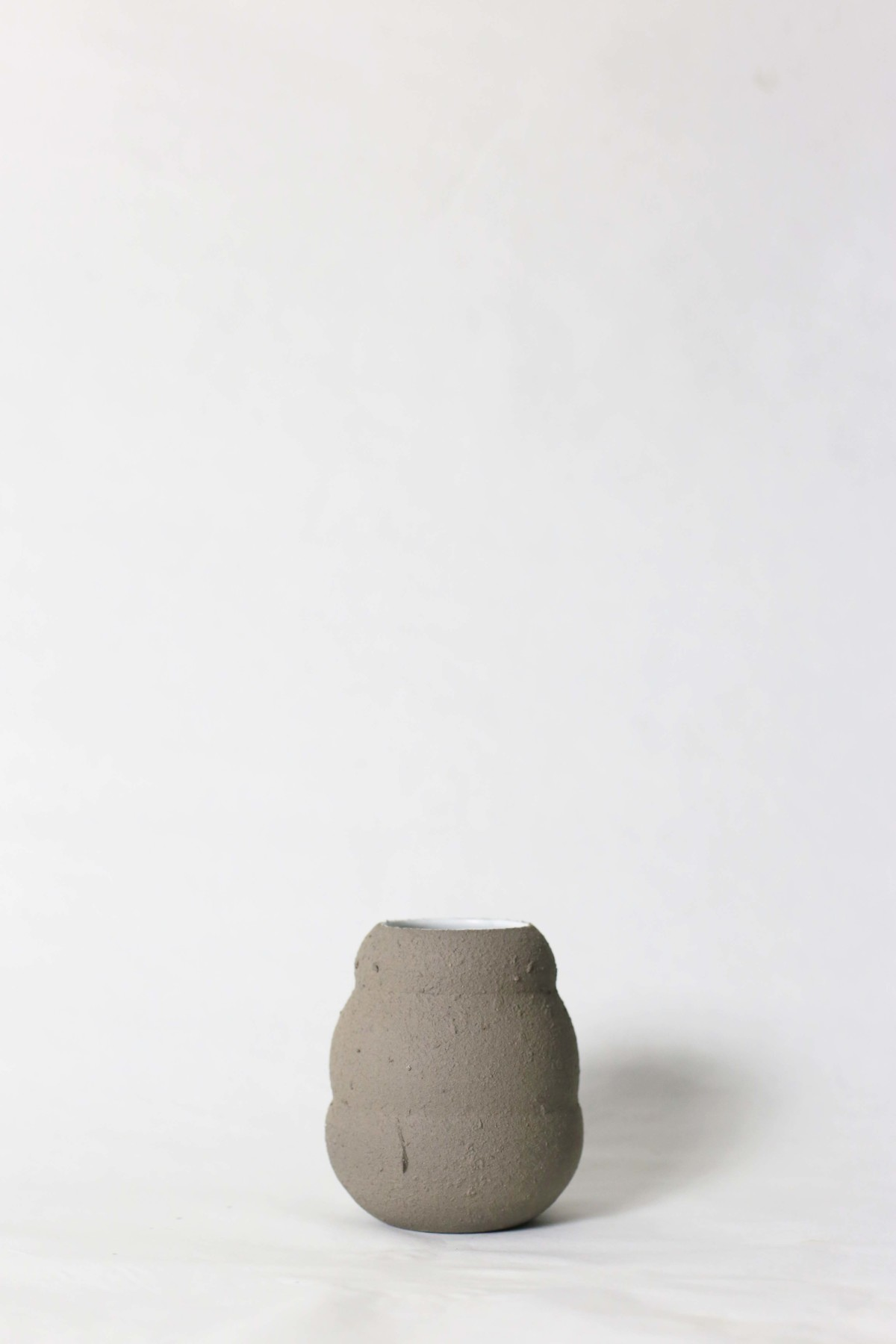 Graphite color ceramic vase in honey pot shape on a white background