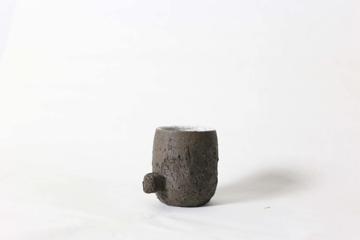 Terra nigra clay cup with a knot bellow on a white background close shot 1