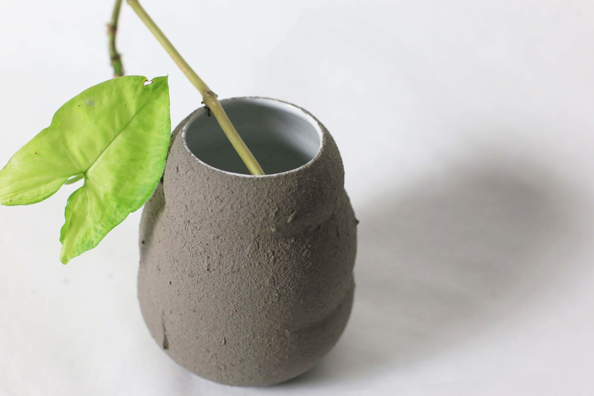 Graphite color ceramic vase in honey pot shape with green leaf on a white background over view 3