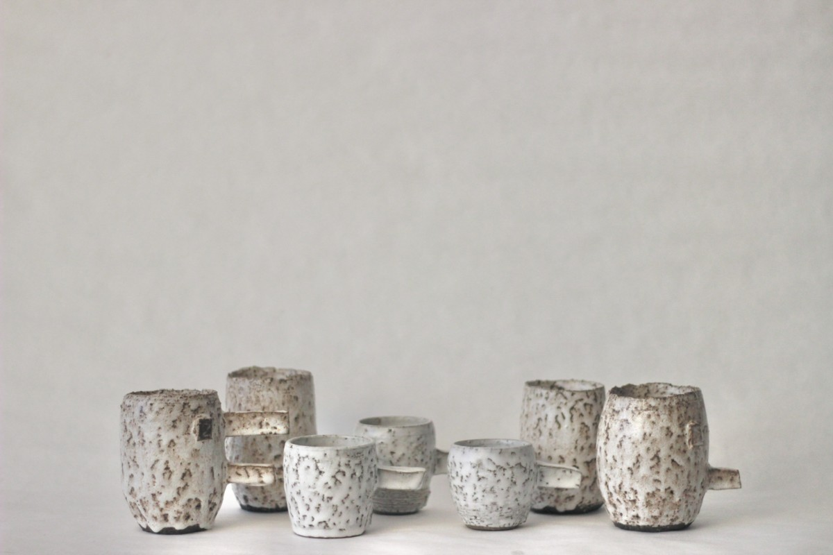 seven spotty glazed ceramic cups on a gray background