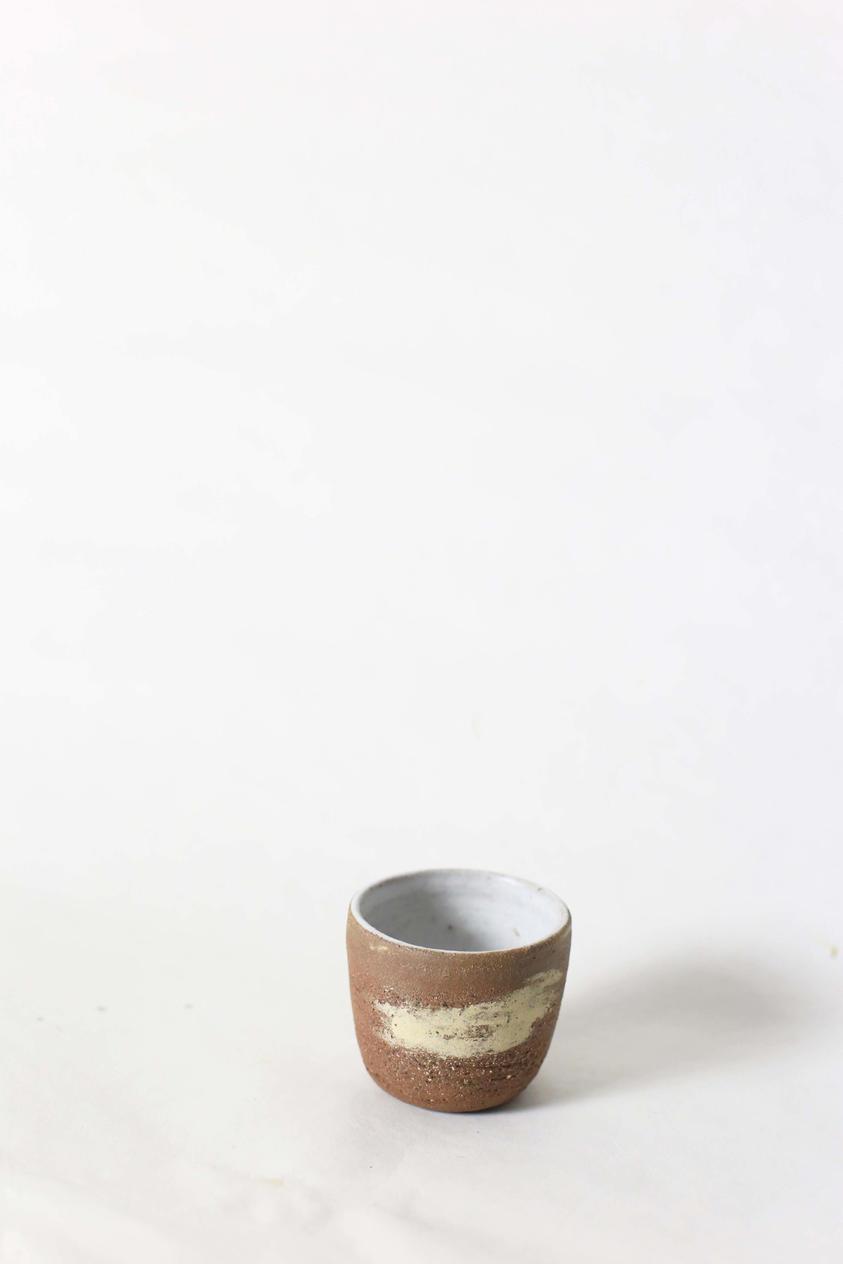 terracotta and sand color clay cup on a white background over view