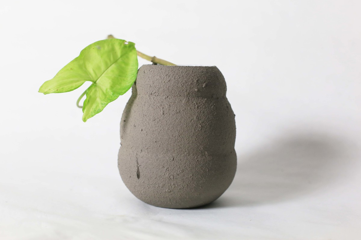 Graphite color ceramic vase in honey pot shape with green leaf on a white background close shot 1