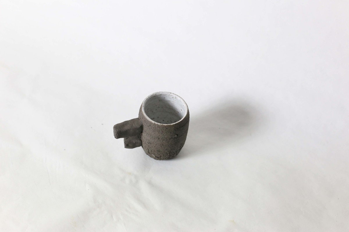 black ceramic cup with two stick handle on a white background over view