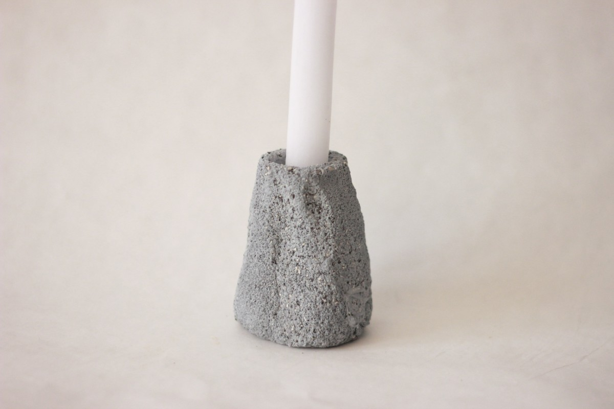 gray ceramic candle holder with candle on gray background close shot