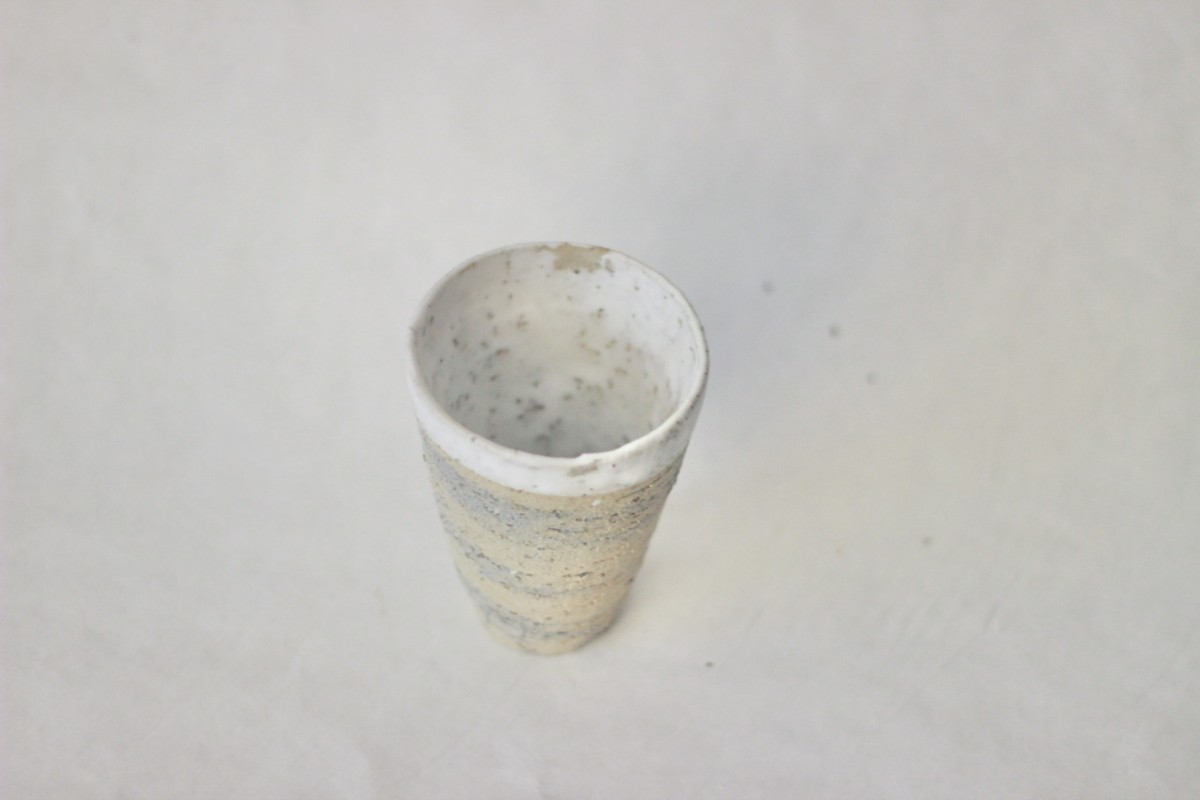 Mixed recycled clay cup on a gray background over view