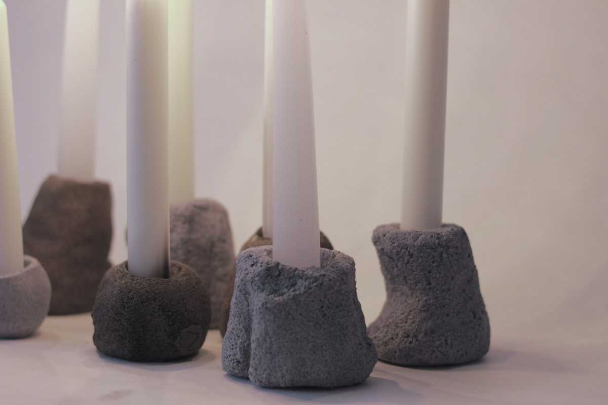 seven ceramic candle holders with lighted candles on a white background
