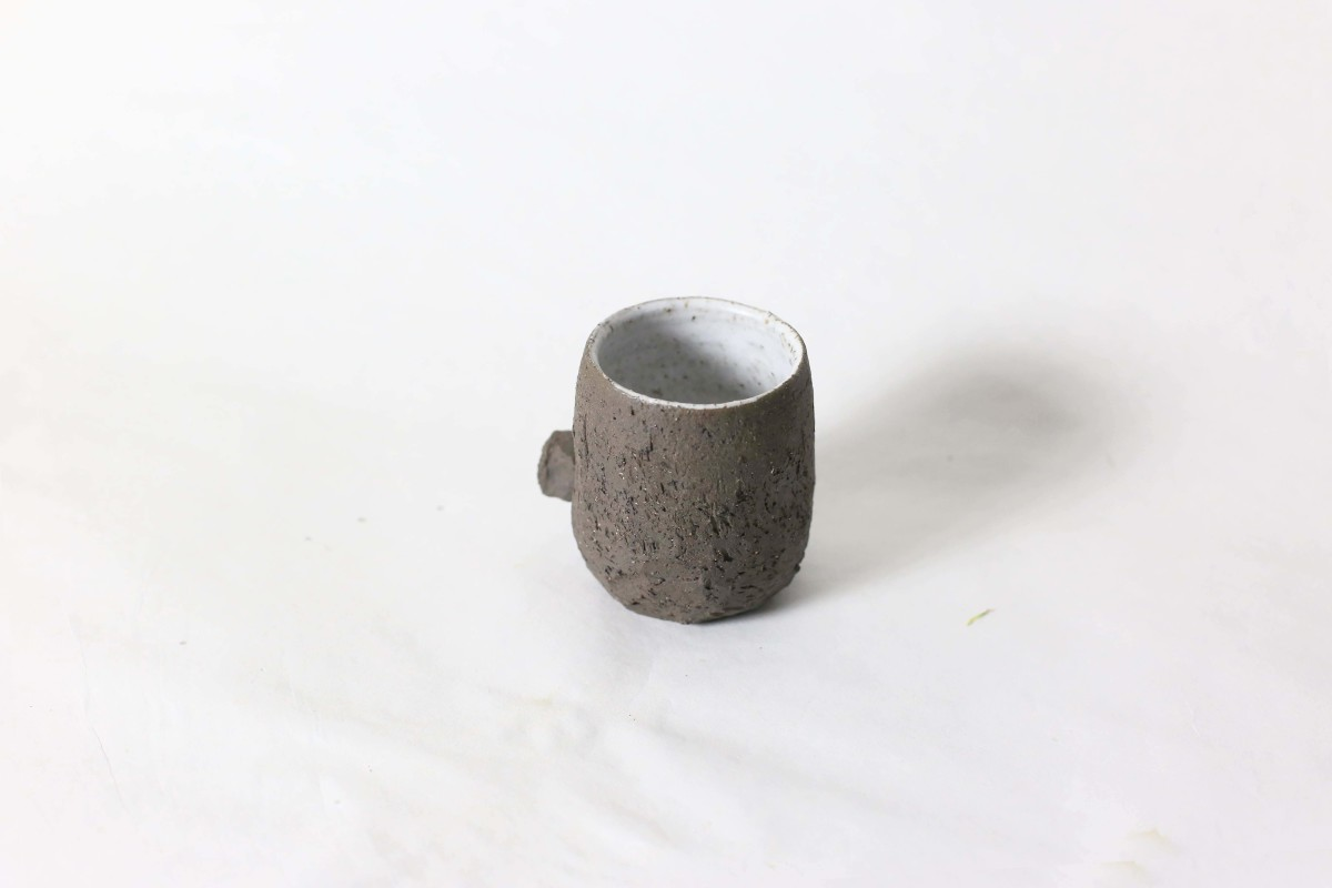Terra nigra clay cup with a knot below on a white background over view 1