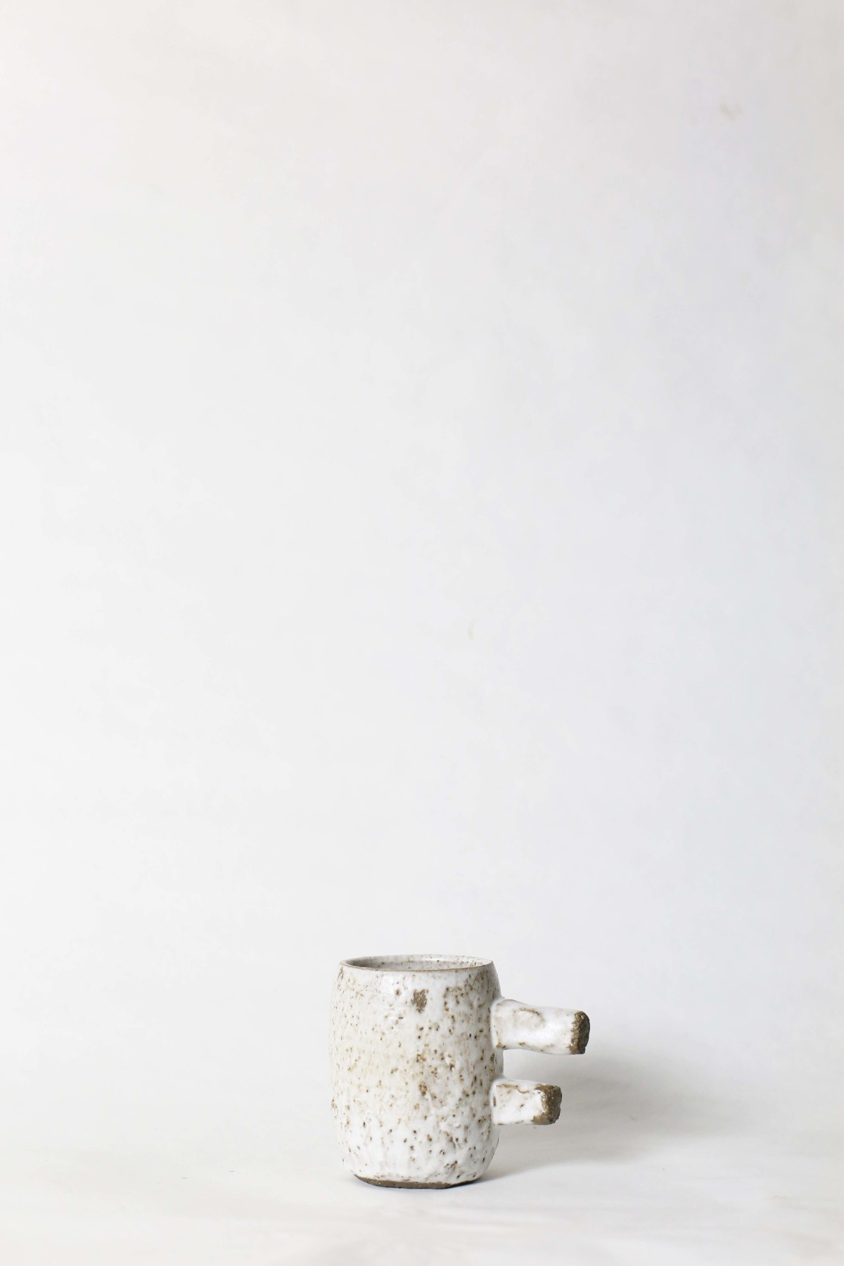spotty white ceramic cup with two stick handle on a white background