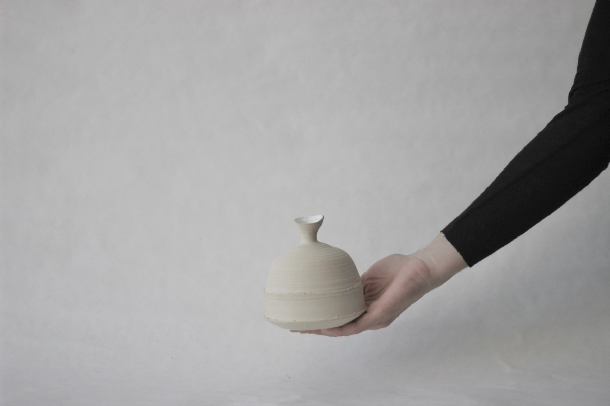a hand holds sand color clay vase on a gray background