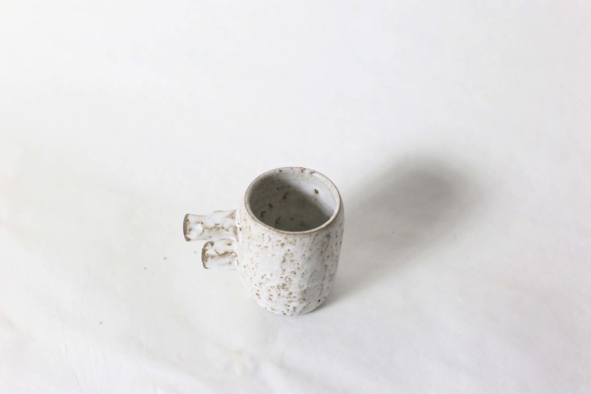 spotty white ceramic cup with two stick handle on a white background over view