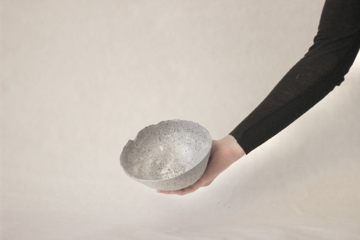a hand holds gray ceramic bowl on a gray background