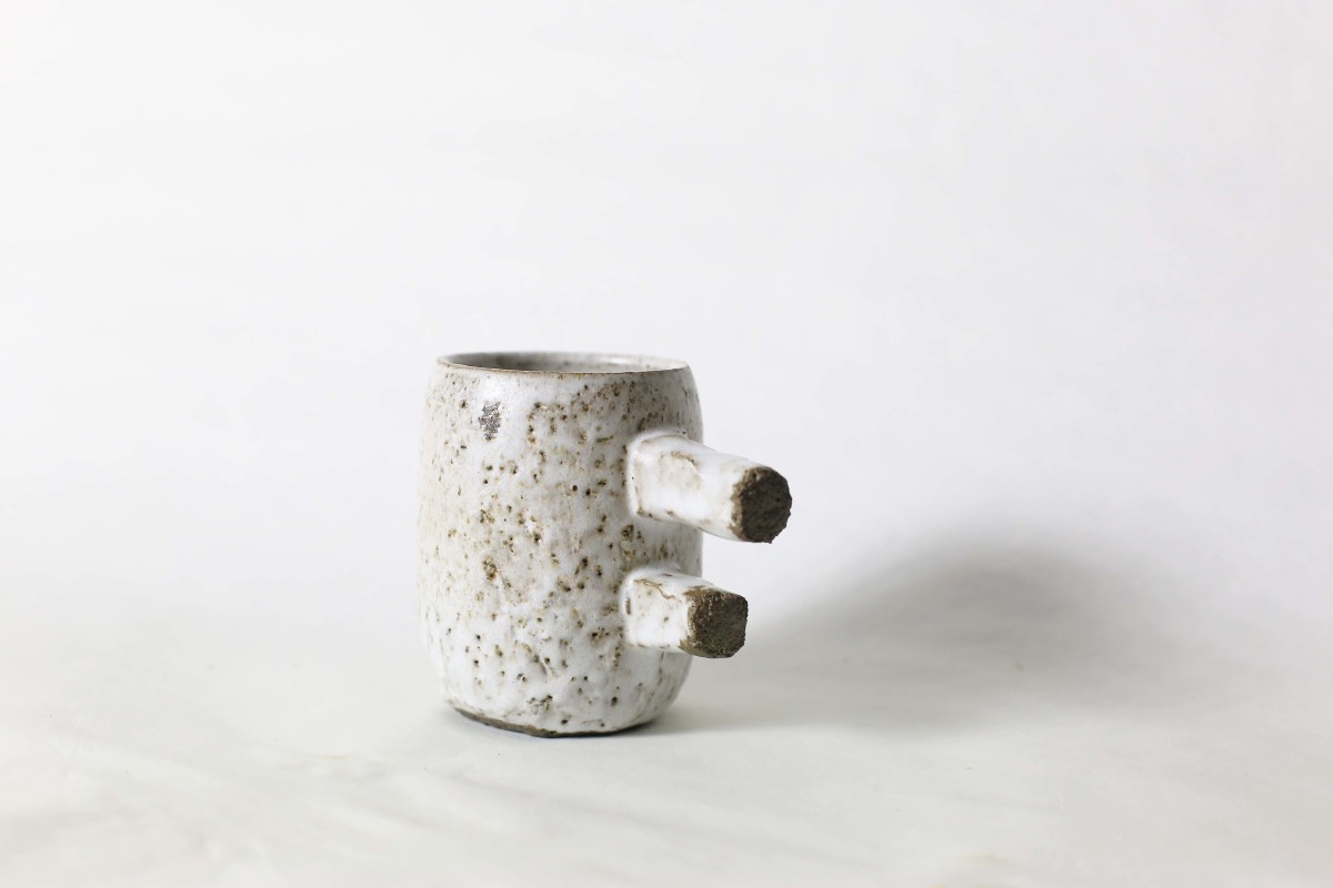 spotty white ceramic cup with two stick handle on a white background close shot 2