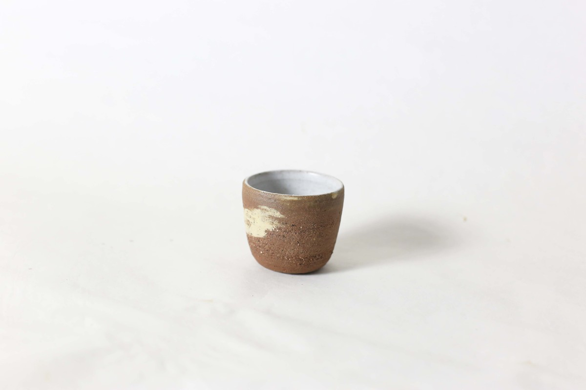 terracotta and sand color clay cup on a white background close shot